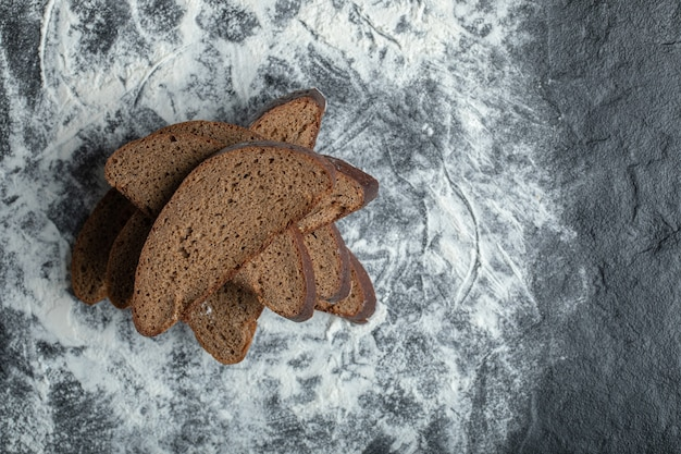 Top view of sliced brown bread on flour background.