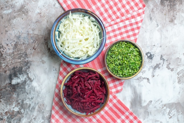 Top view of sliced cabbage with beet and greens on the white surface