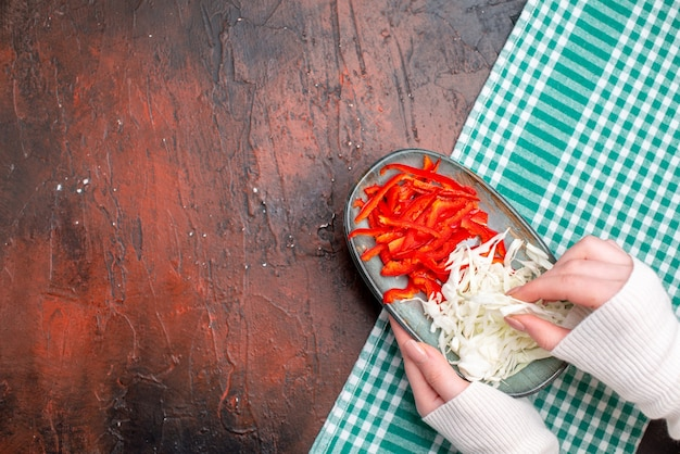 Top view sliced cabbage with bell-pepper on dark table