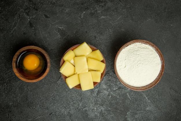 Vista dall'alto di formaggio a fette con farina su sfondo grigio pasta pasto crudo cuocere