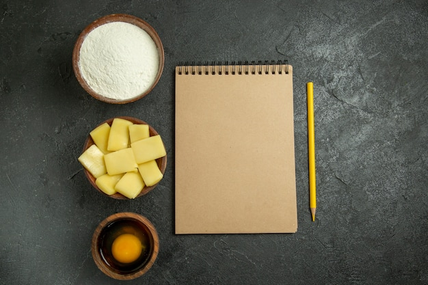 Top view sliced cheese with flour and notepad on grey background dough meal raw food bake