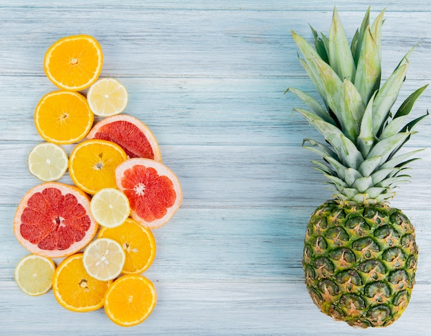 Top view of sliced citrus fruits as orange lemon grapefruit with pineapple on wooden background