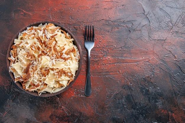 Vista dall'alto di pasta cotta a fette con riso sulla pasta piatto di pasta pasto piano scuro