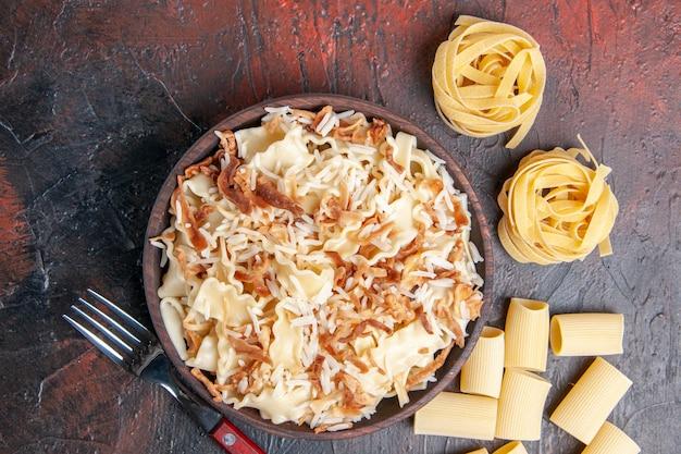 Vista dall'alto di pasta cotta a fette con riso sulla pasta di pasta pasto piatto superficie scura