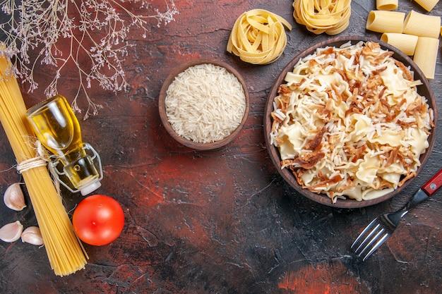 Vista dall'alto di pasta cotta a fette con riso su pasta di pasta piatto superficie scura