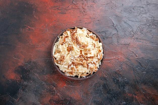 Vista dall'alto di pasta cotta a fette con riso su un piatto di pasta di pasta di superficie scura
