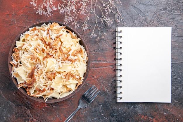 Vista dall'alto a fette di pasta cotta con riso sulla pasta del piatto di pasta del pasto superficie scura