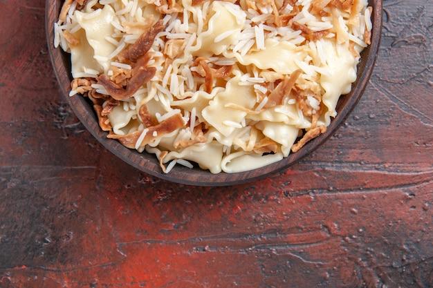 上面図スライスした調理済み生地とご飯を暗い表面の皿生地パスタミールに