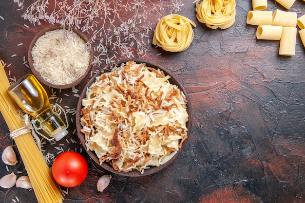 어두운 표면 파스타 접시 반죽 어두운에 쌀과 함께 요리 된 반죽을 슬라이스 상위 뷰