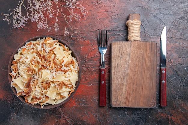 上面図スライスした調理済み生地とご飯をダークデスクミールパスタ皿生地に