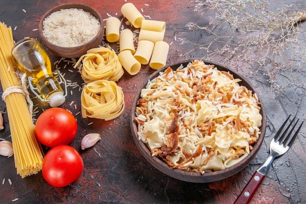 상위 뷰는 어두운 바닥에 쌀과 요리 된 반죽을 슬라이스 파스타 접시 반죽 어두운