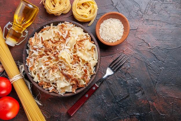 상위 뷰는 어두운 표면 어두운 파스타 접시 반죽에 쌀과 요리 반죽을 슬라이스