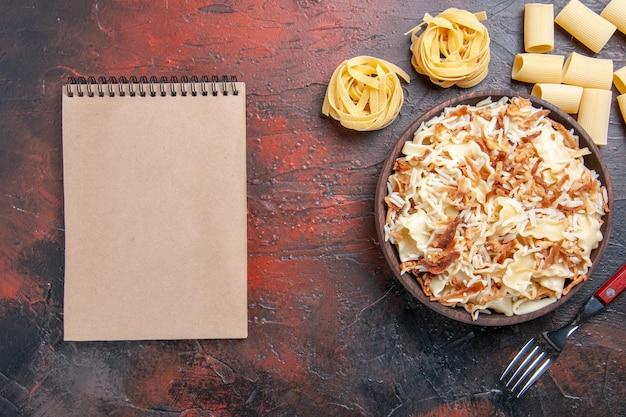 상위 뷰는 어두운 표면 요리 식사 파스타 반죽에 쌀과 함께 요리 된 반죽을 슬라이스