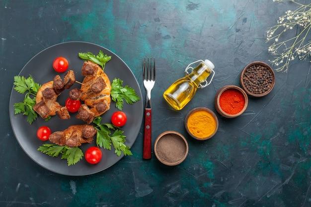 상위 뷰는 파란색 배경에 체리 토마토와 조미료와 함께 요리 된 고기를 슬라이스