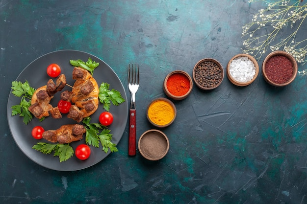 Top view sliced cooked meat with cherry tomatoes and different seasonings on blue background