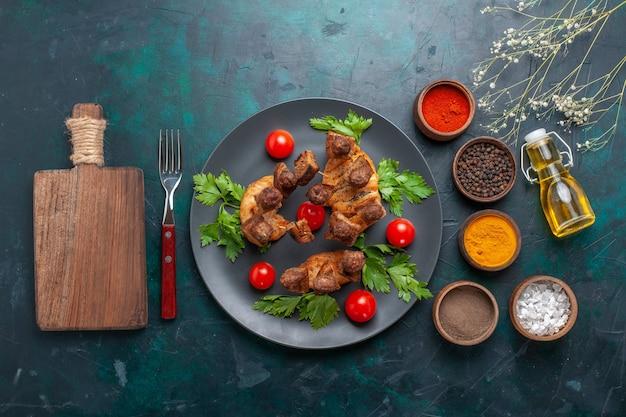 プレートの内側にチェリートマトと青い机の上に調味料を入れた上面スライス調理肉