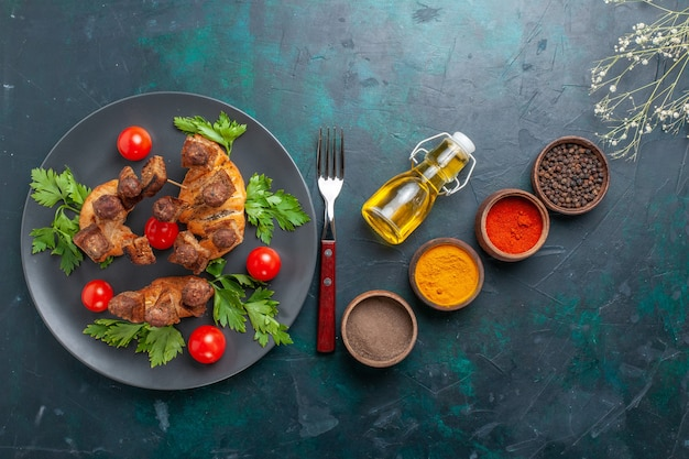 Vista dall'alto affettato di carne cotta con pomodorini e condimenti su sfondo blu