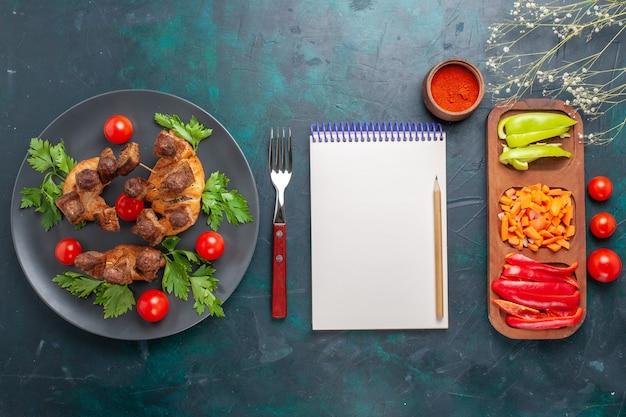 상위 뷰는 파란색 배경에 접시 안에 채소와 체리 토마토와 요리 된 고기를 슬라이스