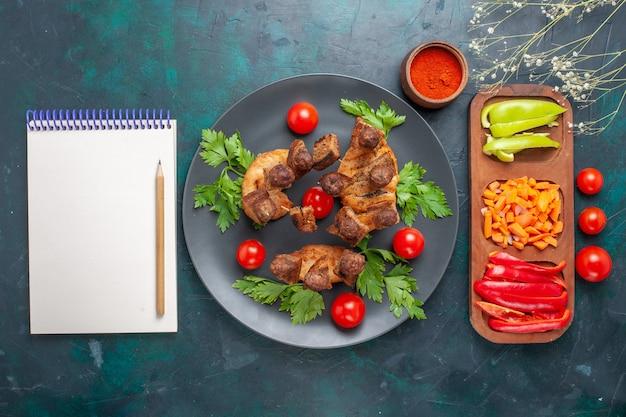 上面図青い机の上のプレートの内側に緑とチェリートマトとスライスした調理済みの肉