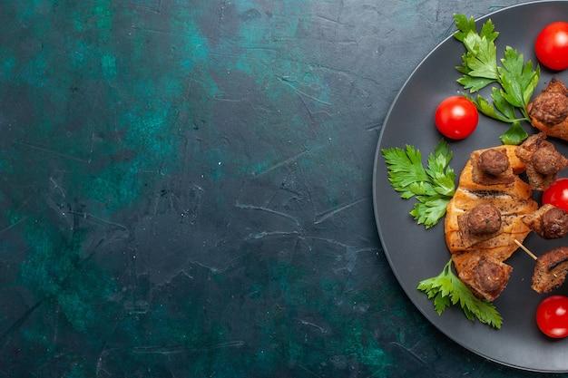 Вид сверху нарезанное приготовленное мясо с зеленью помидоров черри внутри тарелки на темно-синем фоне
