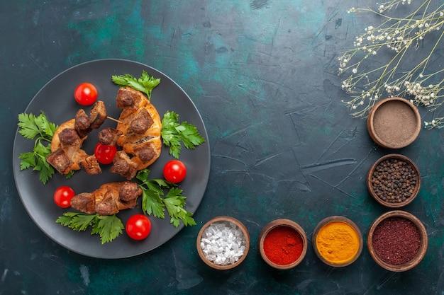 上面図青の背景に調味料と緑とチェリートマトとスライスした調理済みの肉