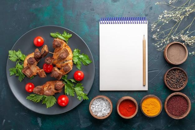 상위 뷰는 파란색 배경에 조미료와 채소와 체리 토마토와 요리 된 고기를 슬라이스