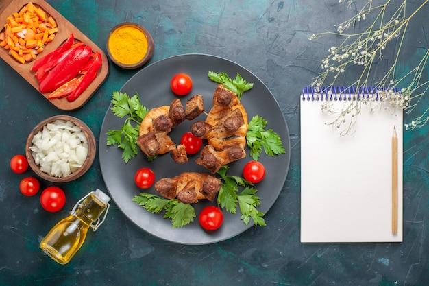 上面図青い机の上にグリーンチェリートマトとオリーブオイルとスライスした調理済みの肉