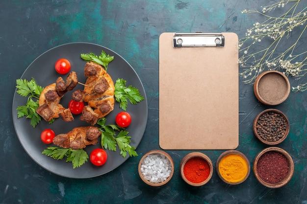 상위 뷰는 파란색 배경에 녹색 체리 토마토와 조미료와 함께 요리 된 고기를 슬라이스