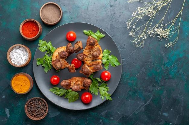 上面図スライスした調理済み肉とグリーンチェリートマトと青い机の上の調味料