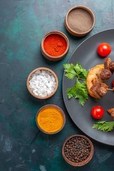 上面図スライスした調理済みの肉と緑のチェリートマトと青の背景に調味料