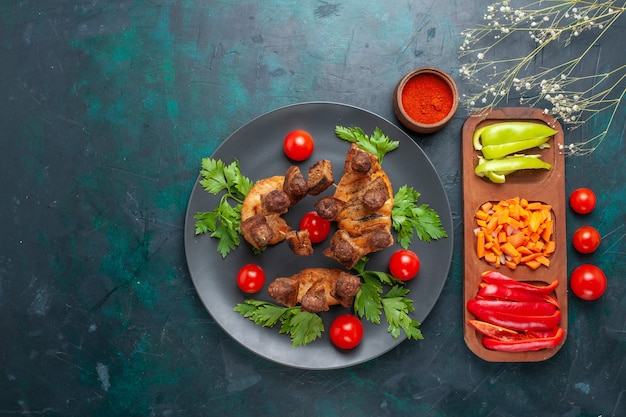 Top view sliced cooked meat with greens and cherry tomatoes inside plate on blue background