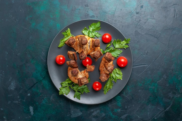Top view sliced cooked meat with greens cherry tomatoes inside plate on the dark-blue background