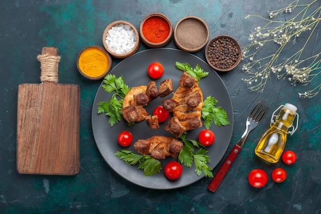 上面図スライスした調理済み肉と緑のチェリートマトオイルと青の背景に調味料