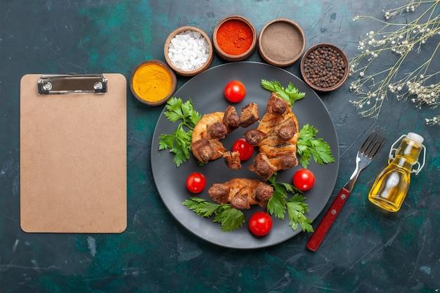 上面図スライスした調理済み肉とグリーンチェリートマトオイルと青い机の調味料