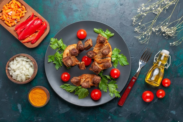 Vista dall'alto affettato di carne cotta con verdi pomodorini olio e condimenti su sfondo blu