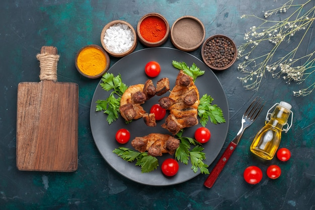 Top view sliced cooked meat with greens cherry tomatoes oil and seasonings on blue background