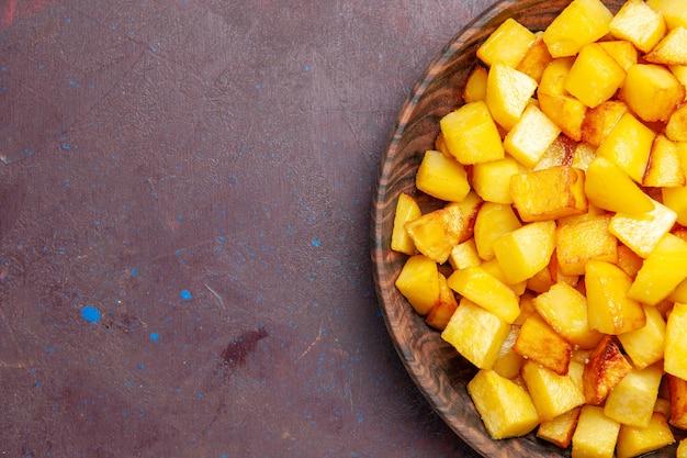Vista dall'alto patate cotte a fette all'interno della piastra marrone sul buio