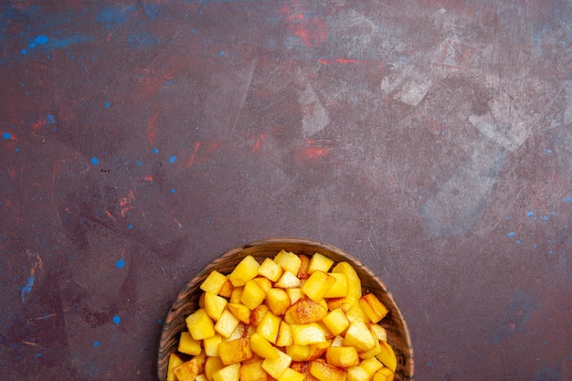 Вид сверху нарезанный вареный картофель внутри коричневой тарелки на темноте