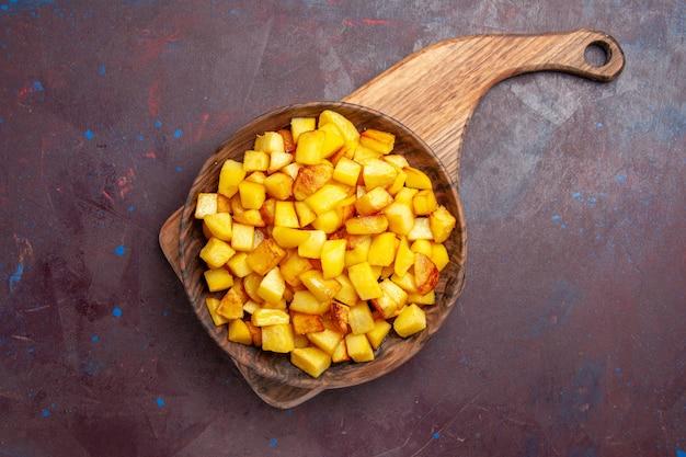 Vista dall'alto patate cotte a fette all'interno del piatto su viola scuro
