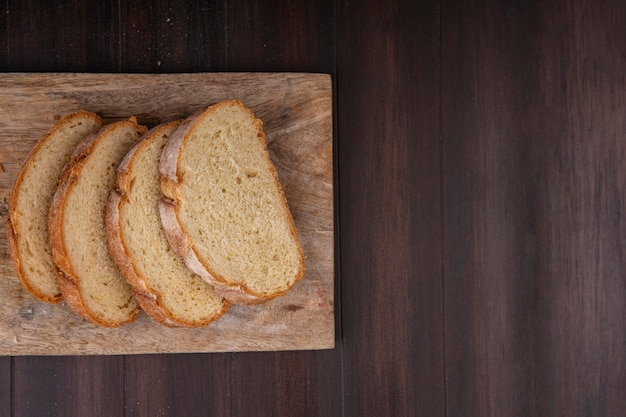 Top view of sliced crusty bread on cutting board on wooden background with copy space