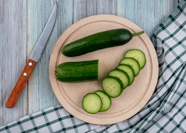 Top view of sliced cucumbers on a stand with a knife on a checkered towel on a gray surface