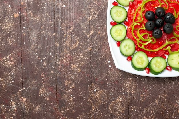Top view sliced cucumbers with olives inside plate on a brown rustic desk diet salad vegetable vitamine health