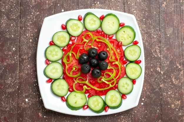 Vista dall'alto cetrioli affettati con olive all'interno della piastra sulla salute di vitamina verdura insalata di dieta rustica marrone scrivania