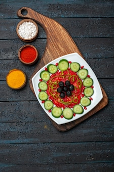 Top view sliced cucumbers with olives inside plate on a dark rustic desk diet salad vegetable vitamine health