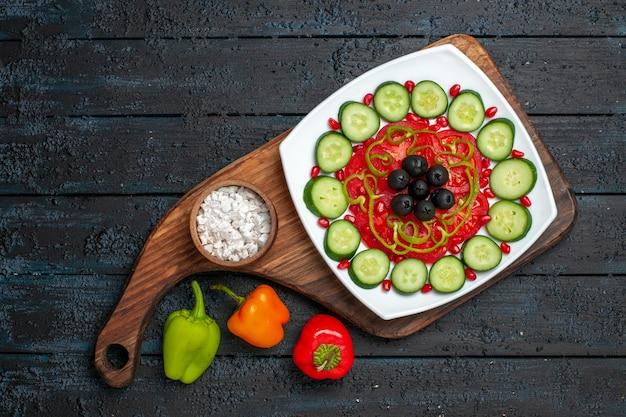 Top view sliced cucumbers with olives inside plate on dark rustic desk diet salad vegetable vitamine health