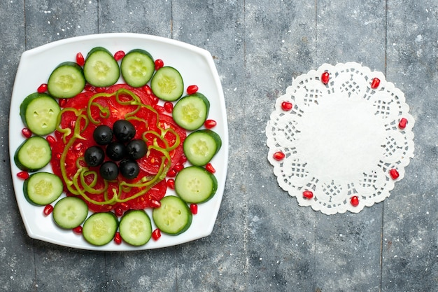 Top view sliced cucumbers with olives inside plate on grey rustic desk salad vegetable vitamine health diet