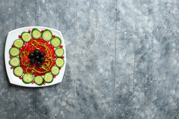 Top view sliced cucumbers with olives inside plate on grey rustic desk salad vegetables vitamine health diet