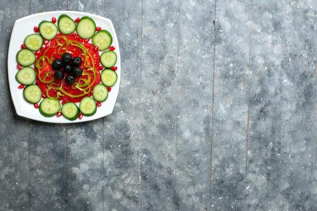 회색 책상 샐러드 야채 색상 비타민 건강 다이어트에 접시 안에 올리브와 함께 상위 뷰 슬라이스 오이