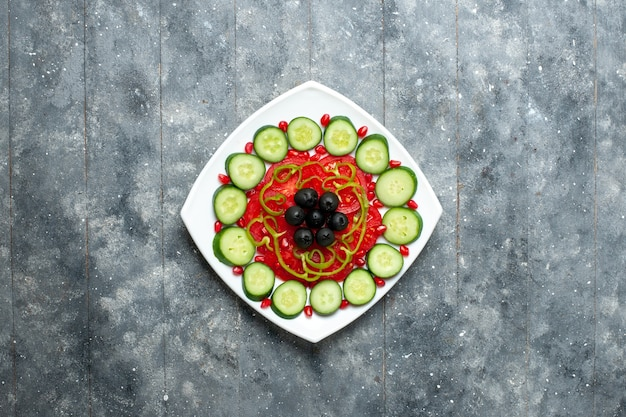 グレーのデスクサラダ野菜色ビタミン健康ダイエットのプレートの内側にオリーブとスライスしたキュウリの上面図