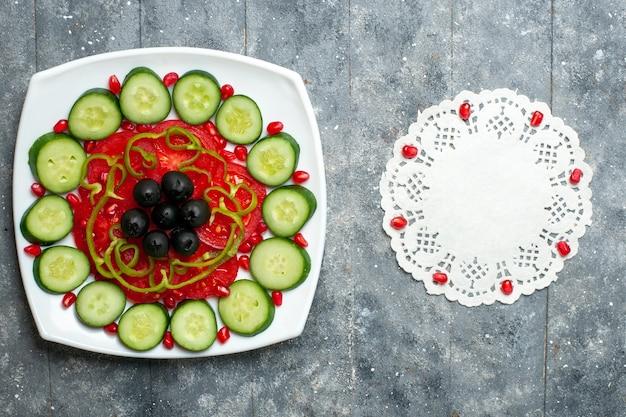 Вид сверху нарезанных огурцов с оливками внутри тарелки на сером деревенском столе салат овощной витамин здоровая диета